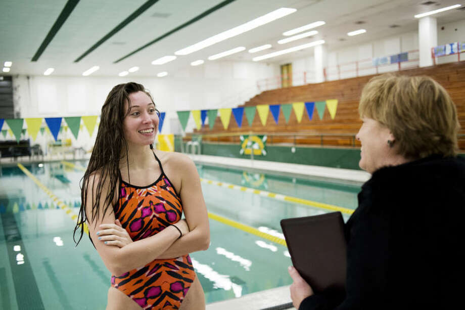 NEIL BLAKE | nblake@mdn.netMidland High senior Abbi Schieber talks to assistant coach Anne Pankratz during practice at H.H. Dow High School on Tuesday. Schieber recently returned to swimming and has broken school records in the pool. Photo: Neil Blake/Midland  Daily News
