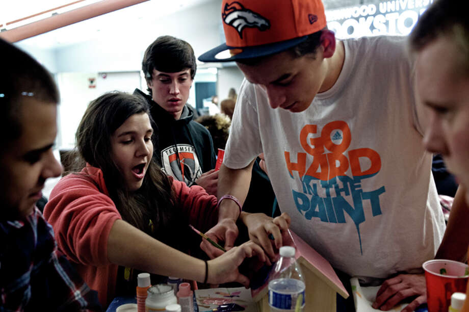 SEAN PROCTOR | sproctor@mdn.net Northwood sophomore Emily Bagwell, of Livonia, works on painting a birdhouse with the help of freshman Lance Copley, of Holly, Tuesday evening during the Habitat for Humanity Birdhouse Building Competition at the Student Union on Northwood's campus, part of Make A Difference Week. Students are spending the week helping the needy in the community, including doing a canned food drive with all proceeds going to the Open Door of Midland County. Photo: Sean Proctor/Midland  Daily News / Midland Daily News