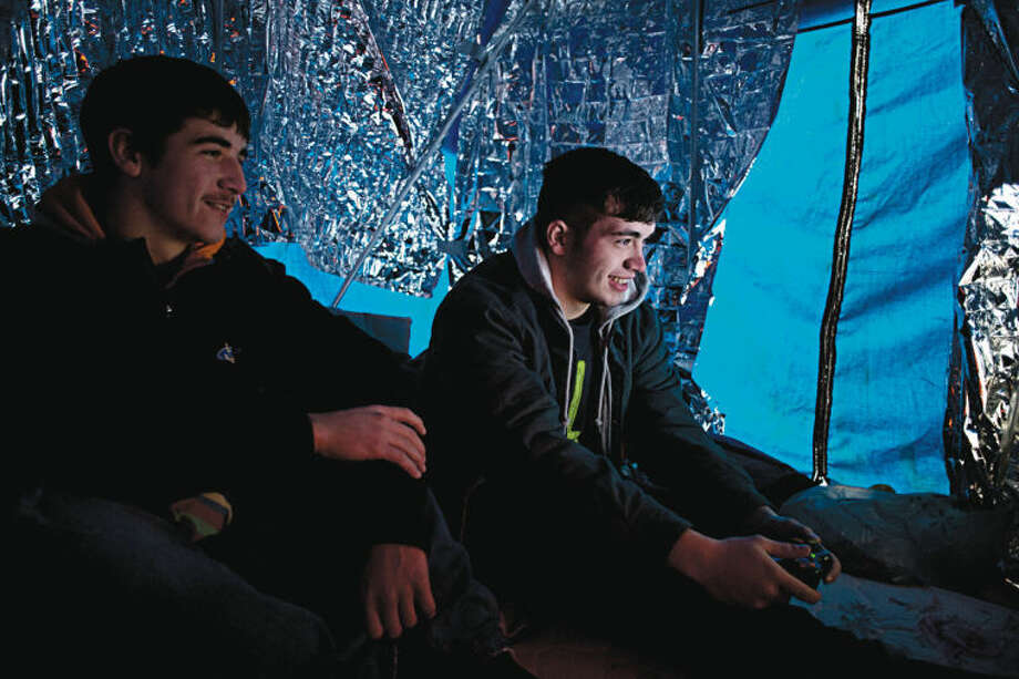 "NEIL BLAKE | nblake@mdn.netMatt Seward, 17, left, and Quayd Short, 18, both of Breckenridge, kill time waiting for Black Friday sales on Tuesday by playing Xbox 360. ""It's not even about (the sales),"" Short said. ""It's tradition."" They are the first in line at Best Buy and set up camp last Friday to hold their spot. Photo: Neil Blake/Midland  Daily News"