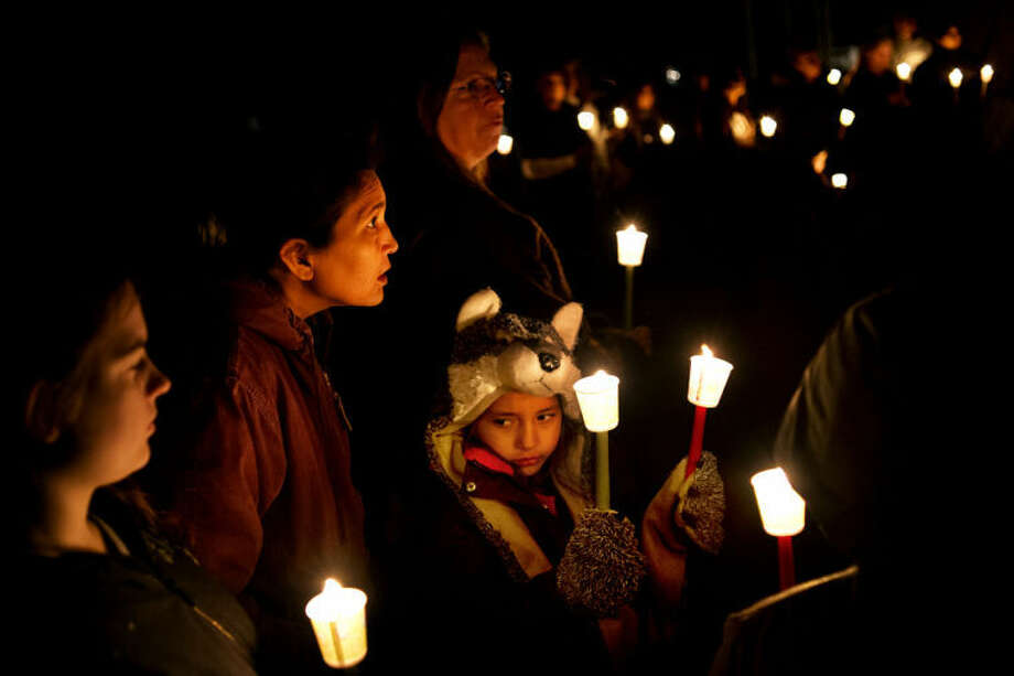 "SEAN PROCTOR | sproctor@mdn.netGlenna Sehl, left, of Mount Pleasant, whispers to her daughter, Sarah Sehl, 7, wearing a wolf hat and gloves, during a candlelight vigil for the wolf population of Michigan. ""We're stepping up for our brothers, they don't have voices,"" Glenna said. Photo: Sean Proctor/Midland  Daily News"