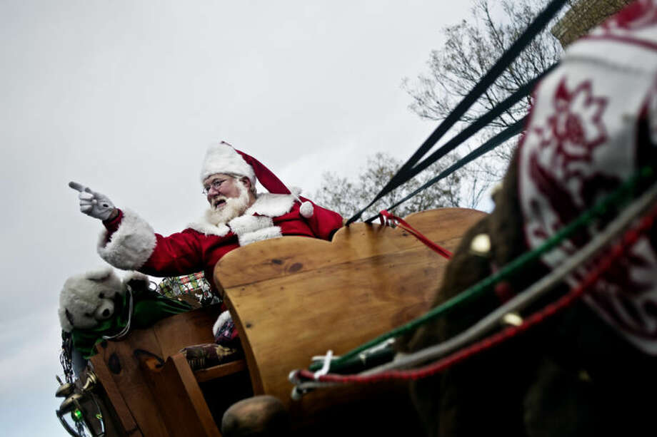 SEAN PROCTOR | sproctor@mdn.netSanta Claus waves to bystanders lining Main Street during the Midland Santa Holiday Parade on Saturday. The parade started at Midland High School and ended in downtown. Photo: Sean Proctor/Midland  Daily News