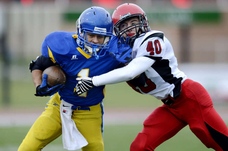 NICK KING | nking@mdn.netMidland's Jukarri Cooper, left, is tackled by Marquette's Trevor Koski after a catch during the first quarter Saturday at Midland Community Stadium. The Chemics won 41-10. Photo: Nick King/Midland  Daily News