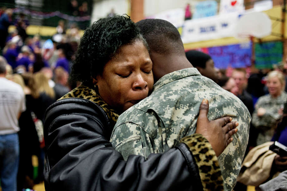 Emily Spraggins of Flint hugs her son, Specialist Anthony Morris, after the 1460th Transportation Company departure ceremony at H.H. Dow High School on Saturday. Photo: Neil Blake/Midland  Daily News / Midland Daily News