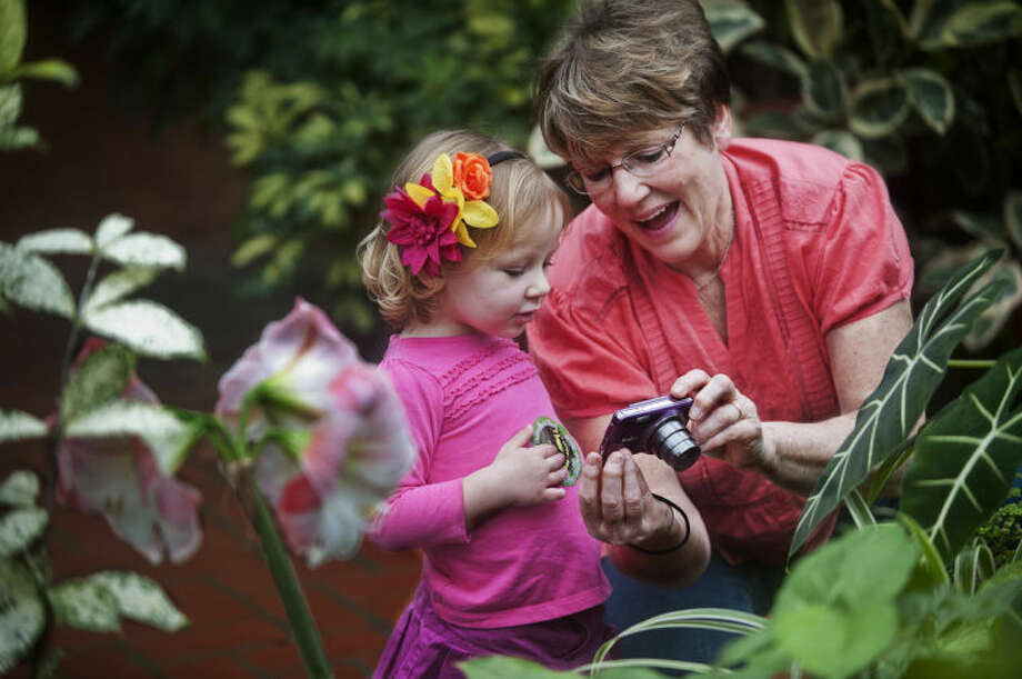 ZACK WITTMAN | For the Daily NewsMaureen Bekhart, of Essexville, shows her granddaughter, Autumn Lyons, 2, of Bay City, a photo of a butterfly she took at the Dow Gardens conservatory.