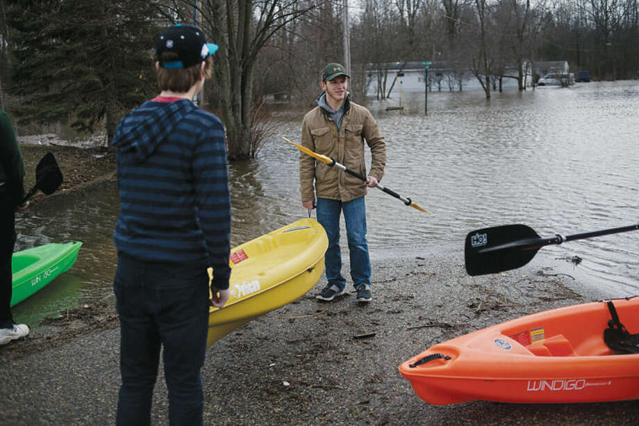 NEIL BLAKE | nblake@mdn.netTyler Hill, 17, of Sanford, center, gets help hauling a kayak to the water's edge from Sam Whitman, 15, of Sanford, in Sanford on Friday. Hill and a few friends kayaked through the floodwaters to his house to check on the property. Photo: Neil Blake/Midland  Daily News