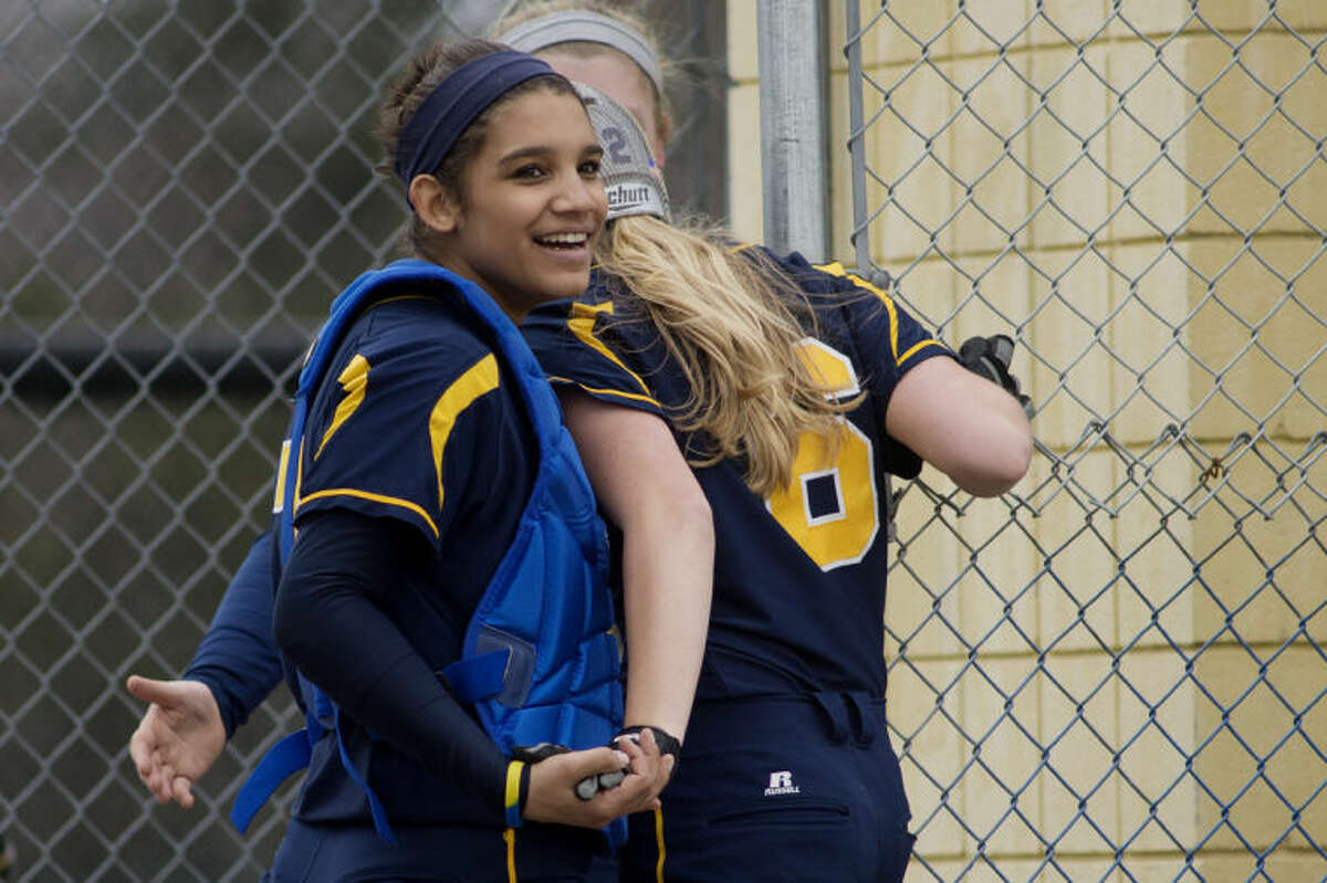 NEIL BLAKE | nblake@mdn.netMidland catcher Bry Collins congratulates Kelsey Pohl after Pohl scored during the first game of a double header against Davison at Midland High School on Monday.