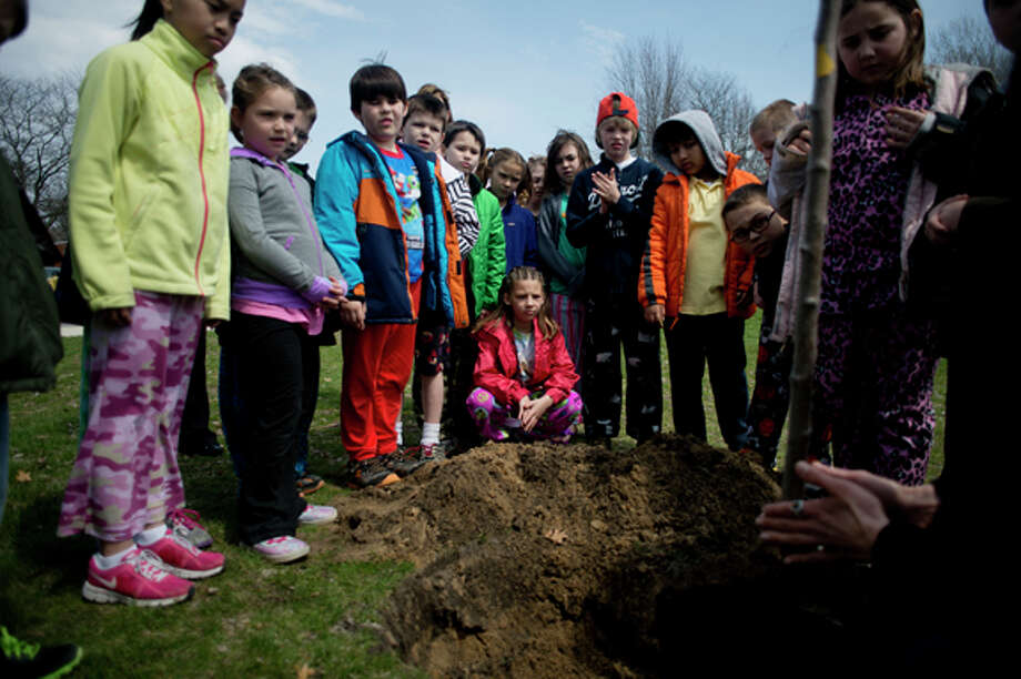NEIL BLAKE | nblake@mdn.net Woodcrest Elementary third grader Brooke Seymour, crouched center, listens with the rest of Katherine Metiva's class to Stephanie Szostak, the horticulturist with the Midland Parks and Recreation Department, talk about tree planting at Woodcrest on Friday. City employees helped four third grade classes at Woodcrest plant ornamental pear trees in honor of Arbor Day. Photo: Neil Blake/Midland  Daily News / Midland Daily News