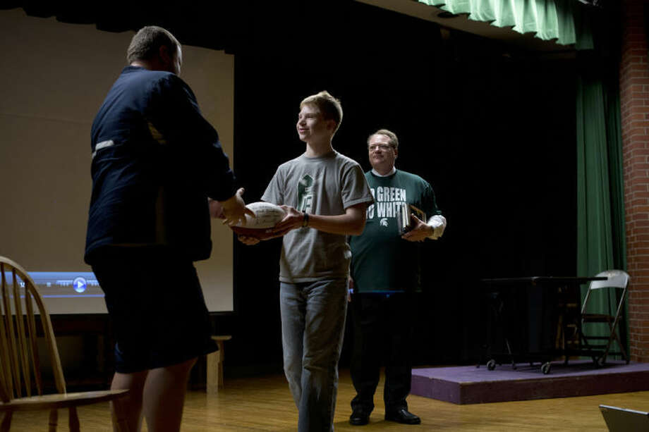 NEIL BLAKE | nblake@mdn.netNortheast Middle School eighth-grader Adam White and his father, Paul White, present Northeast paraprofessional Ched Johnson with a football signed by Michigan State University football coach Mark Dantonio and quarterback Andrew Maxwell on Tuesday. Dantonio and Maxwell also made a video voicing their recognition of Johnson's leadership and service as a coach through the years.
