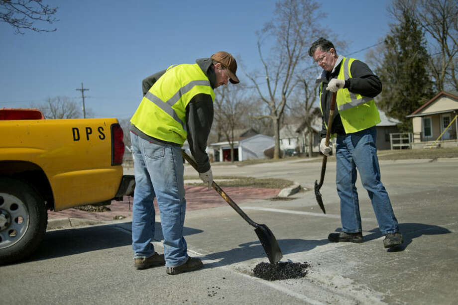 NICK KING | nking@mdn.netCity of Midland workers Bob Hunter, left, and Steve Gomobsi fill in a pothole on Lincoln Street in Midland. City crews use a heated tar mixture to fill in spots on roads when problem areas are brought to their attention. Photo: Nick King/Midland  Daily News