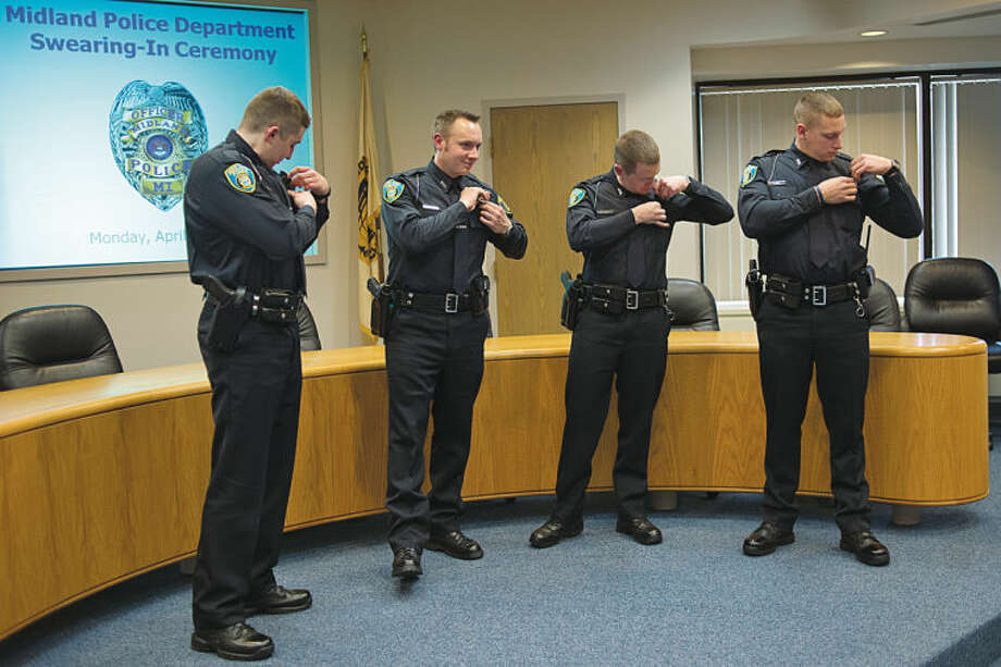 NICK KING | nking@mdn.netFrom left, Travis Toth, Neil Wahnefried, Lucas Huss and Mitchell Eddy adjust their badges after the four were sworn-in as Midland Police officers earlier this week during a ceremony at City Hall. Photo: Nick King/Midland  Daily News