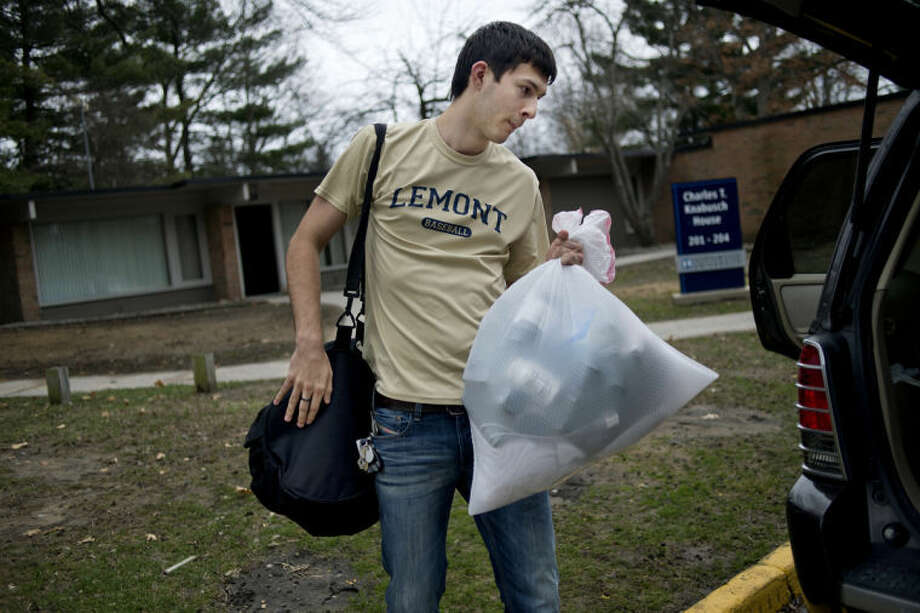NICK KING | nking@mdn.netNorthwood junior Mike Meyer moves his belongings from his apartment to a friend's car at the Charles T. Knabusch House on the Northwood campus on Wednesday. Meyer heard of the potential flooding and he and roommate Jameson Tomaski decided to evacuate. Meyer is going to spend some time at home in Florida and Tomaski is going to stay with family nearby. Photo: Nick King/Midland  Daily News