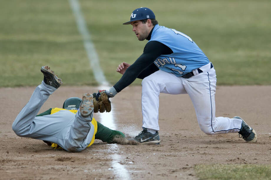 NICK KING | nking@mdn.netNorthwood's Jason Fracassa, right, attempts to tag out Wayne State's Eric Cunningham at third base in the third inning Sunday at Gerace Stadium. Photo: Nick King/Midland  Daily News