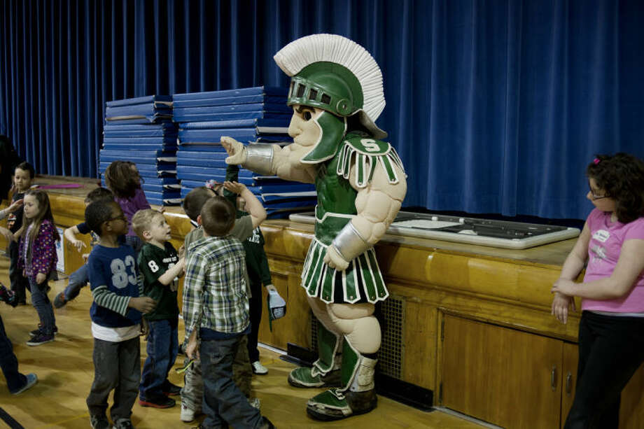 NEIL BLAKE | nblake@mdn.netSparty, Michigan State University's mascot, high fives young fans during his visit to Eastlawn Elementary School in Midland on Friday. Photo: Neil Blake/Midland  Daily News