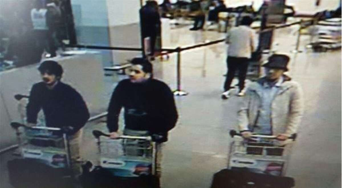A picture released on March 22, 2016 by the belgian federal police on demand of the Federal prosecutor shows a screengrab of the airport CCTV camera showing three suspects of this morning's attacks at Brussels Airport, in Zaventem. Two explosions in the departure hall of Brussels Airport this morning took the lives of 14 people, 81 got injured. Government sources speak of a terrorist attack. The terrorist threat level has been heightened to four across the country.