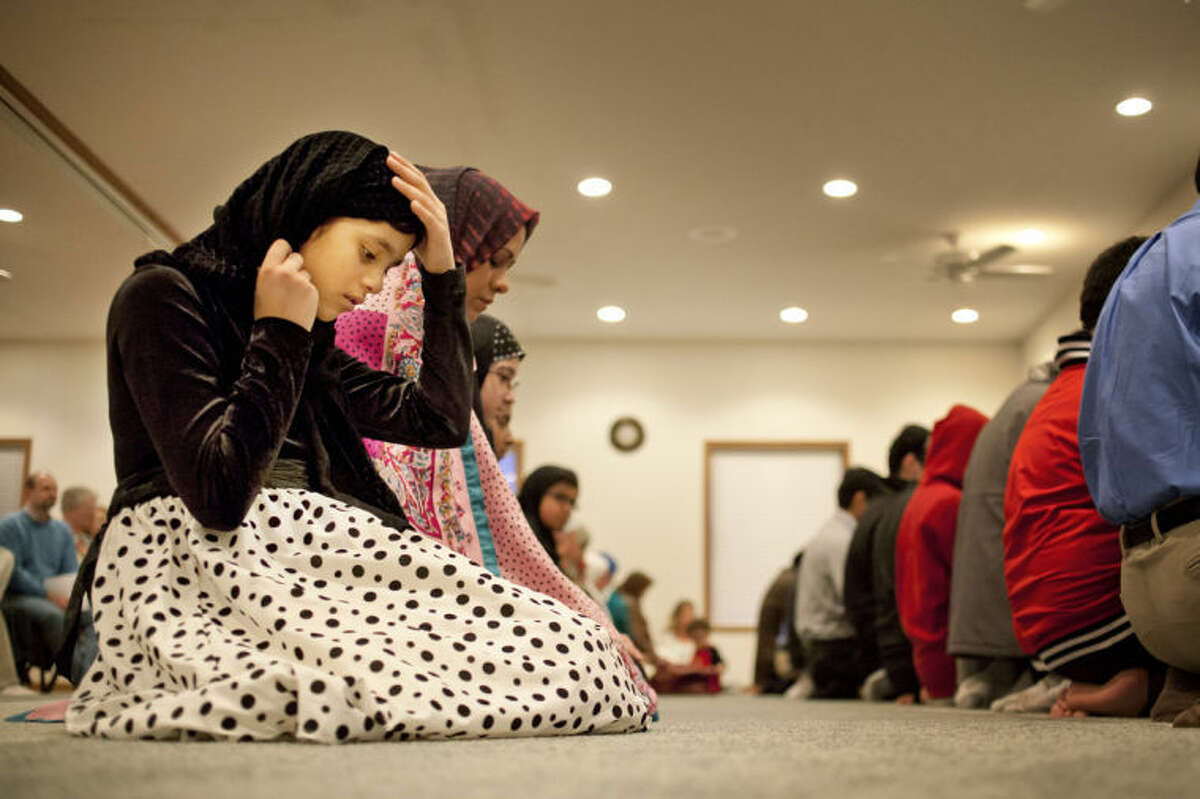 """JEFFREY SMITH   for the Daily NewsMehvish Khan, 8, of Midland, participates in a call to prayer during the """"Choosing a Culture of Understanding"""" series Friday evening at the Islamic Center of Midland."""