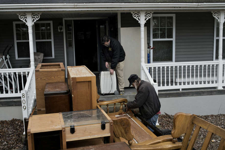 SEAN PROCTOR | sproctor@mdn.netJim Kast, center, and Mike Ginter, of Midland, work on loading a trailer full of items from Ginter's house to take to a safer location Wednesday afternoon in preparation for the potential flooding. While bigger items including furniture and lawn equipment were taken elsewhere, smaller items including clothes and books were stored upstairs. Photo: Sean Proctor
