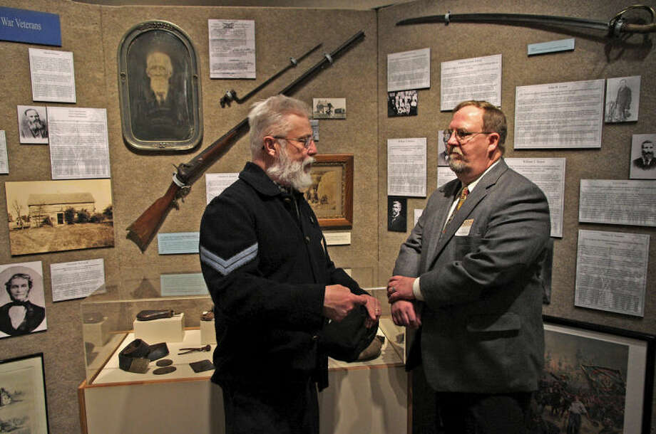 STUART FROHM | for the Daily NewsTom Cherry wears a reproduction of a Civil War Union corporal's uniform as he and Randy Schoen converse Thursday at the opening reception of the exhibit on Midland County's Civil War legacy. Cherry, of Geneva Township, is a member of the North-South Skirmish Association, whose members competitively fire real and replica Civil War handguns, long guns and artillery pieces. He helped identify weapons loaned for the exhibit. Schoen is a volunteer who worked on the exhibit, which runs through Oct. 26 at the Herbert D. Doan Midland County History Center, 3417 W. Main St. The former Civil War corporal in the large photograph behind Cherry is Charles A. Kinney, a Larkin Township farmer who died in 1916 at age 79. Photo: STUART M. FROHM