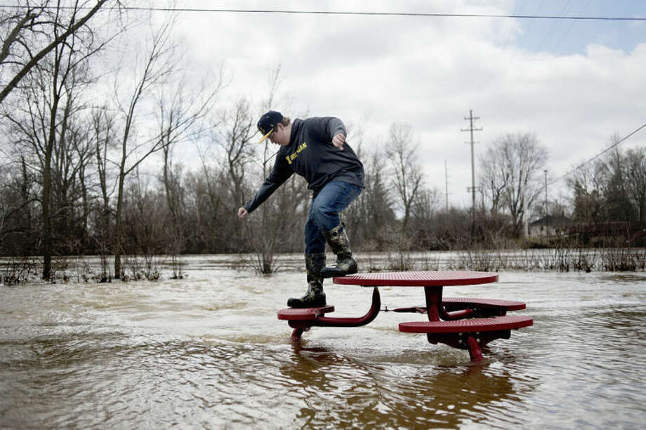 SEAN PROCTOR | sproctor@mdn.netAaron Kielpinski, 14, of Midland, climbs off a picnic table and back into the flood waters at the Midland Farmer's Market on Saturday afternoon. The Tittabawassee River crested during the early morning hours at 28.37 feet, and area residents braved the chilly weather to observe the slowly receding flood waters. Photo: Sean Proctor