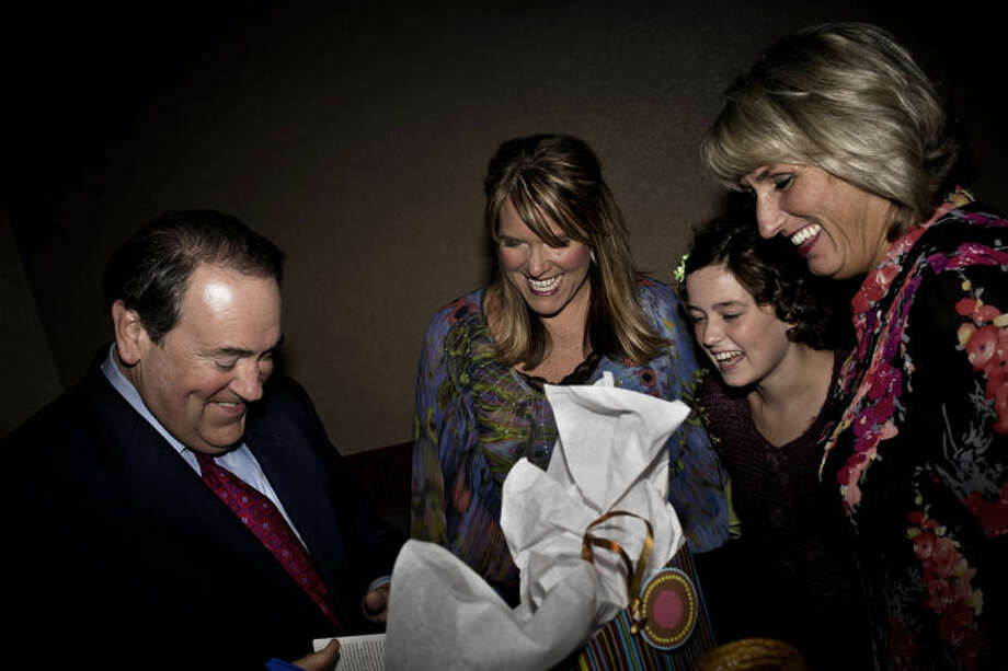 SEAN PROCTOR | sproctor@mdn.netFormer Arkansas governor and presidential candidate Mike Huckabee opens a gift given to him by Sarah Schieber, center, Mary Juengel, and her mother Marni Juengel containing music by Schieber and Juengel Thursday evening at Valley Plaza during the annual Pregnancy Resource Center fundraising banquet. According to executive director Heather Fisher, a board member turned on the TV one night to see Huckabee talking about the value of human life on his television show, and they decided to pursue him as a speaker. Photo: Sean Proctor/Midland  Daily News