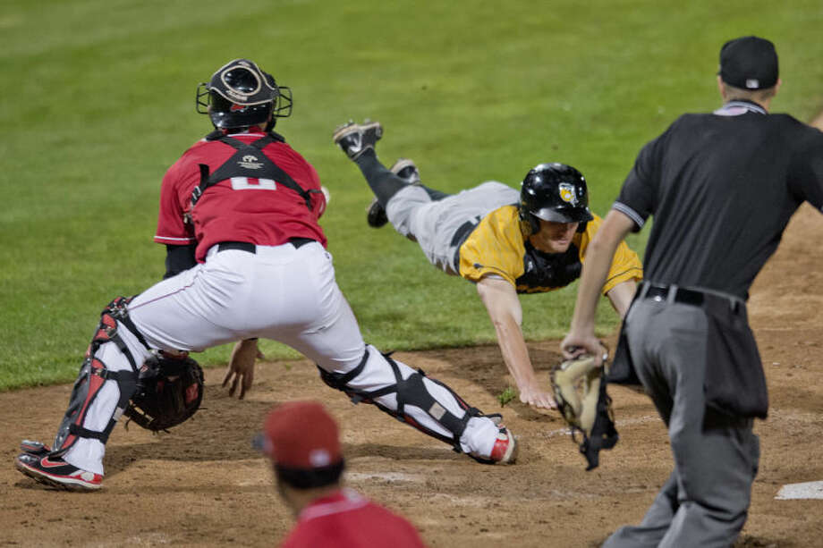 NICK KING | nking@mdn.netSilver Hawks' Michael Lang, center, dives for home plate to score a run as Loons' catcher Jose Capellan, left, waits for the ball during the eighth inning Wednesday at Dow Diamond. The Silver Hawks beat the Loons 3-0. Photo: Nick King/Midland  Daily News
