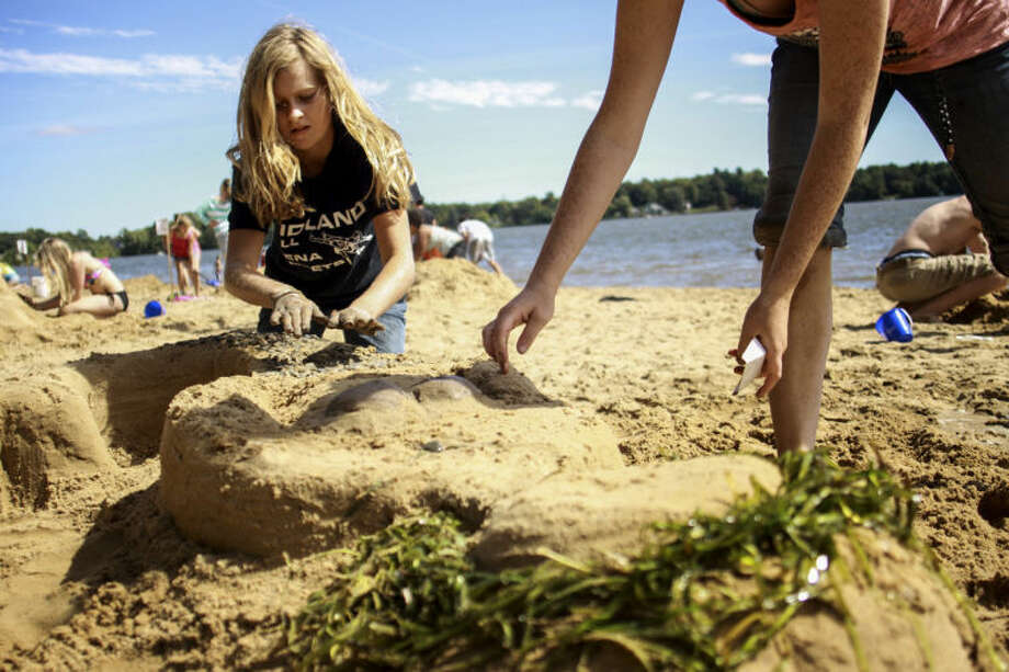 Charlotte Bodak | Midland Daily NewsKirklynn Miller, 16, of Ohio, places pebbles on top of a mermaid she is working on with her sister for the sand castle building contest during Parkapalooza at Sanford Lake Park Sunday.