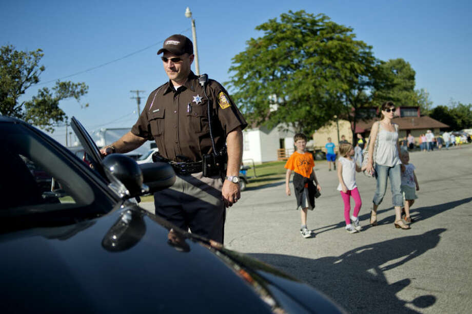 NICK KING | nking@mdn.netTim Kaminski, left, a reserve deputy with the Midland County Sheriff's Office, opens the door to a cruiser during his shift recently at the Midland County Fair. Photo: Nick King/Midland  Daily News
