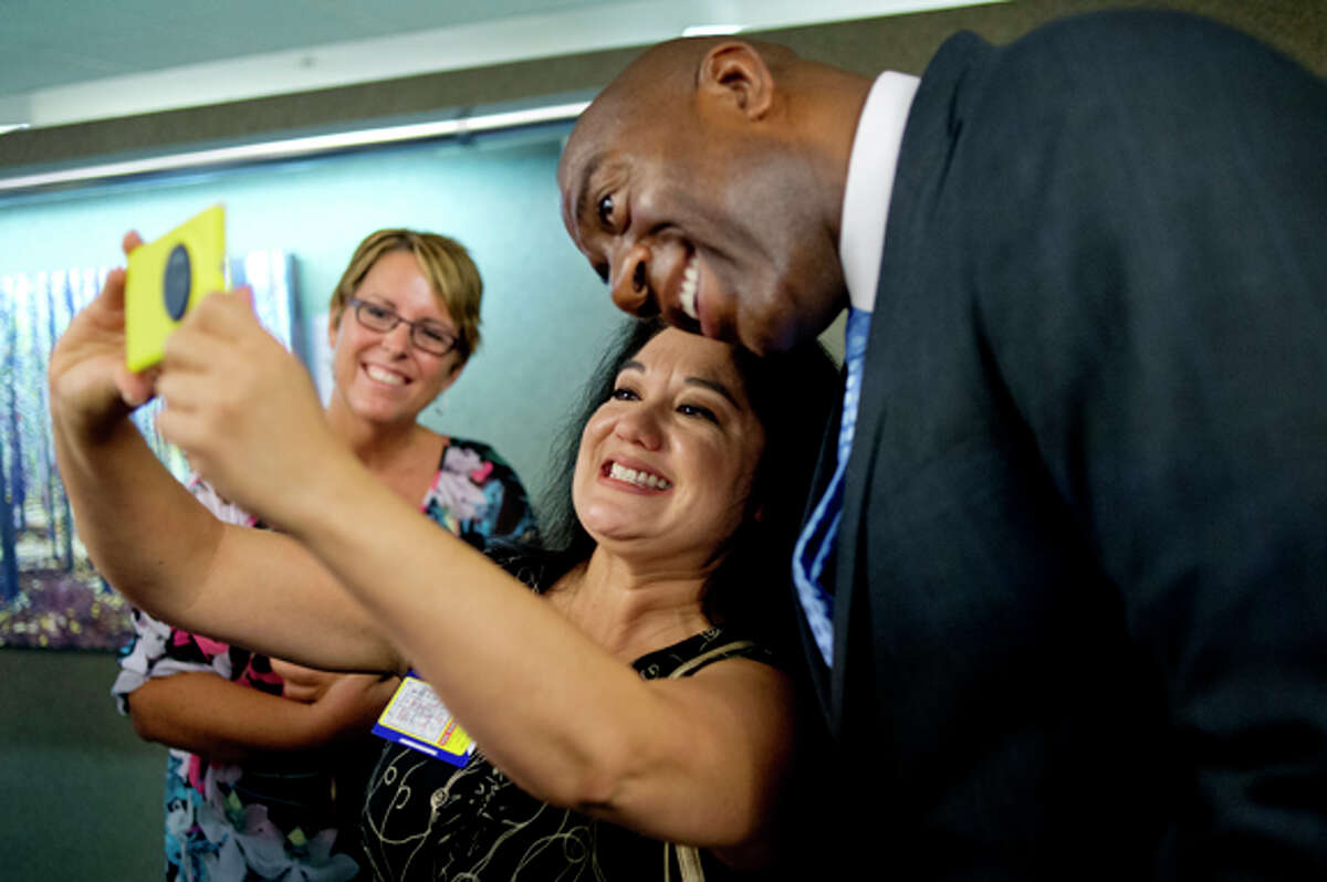 Hemlock Semiconductor Group employee Denise Timm, of Freeland, takes a photo of herself and Earvin Magic Johnson Friday at the Dow Corning Corporate Center after Johnson's talk. Dow Corning employee Erin Chatterton looks on in the background. Magic spoke to employees and Saginaw area high school students, answered questions, posed for photos and signed autographs. Dow Corning is one of several Great Lakes Bay Region companies partnering with Magic Johnson in support of the Saginaw Promise Zone initiative.