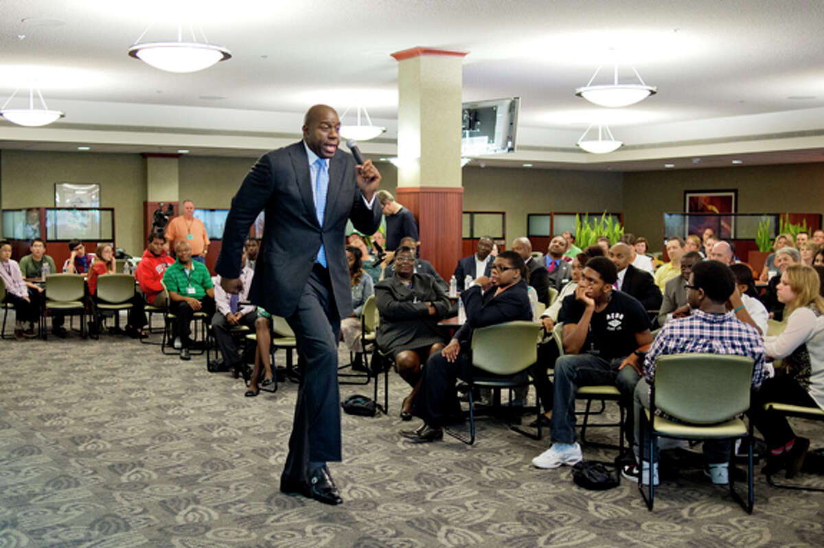 NICK KING | nking@mdn.net Earvin Magic Johnson acts out a play between himself and Larry Bird Friday at the Dow Corning Corporate Center. Magic spoke to employees and Saginaw area high school students, answered questions, posed for photos and signed autographs. Dow Corning is one of several Great Lakes Bay Region companies partnering with Magic Johnson in support of the Saginaw Promise Zone initiative.