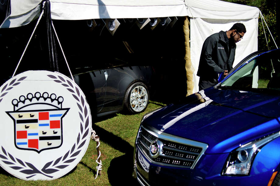 NICK KING | nking@mdn.net Sophomore Kevin Brown opens the door to a 2014 Cadillac ATS AWD 2.0T Luxury Collection at the Cadillac display during the Northwood University Auto Show Friday on campus. Photo: Nick King/Midland  Daily News / Midland Daily News
