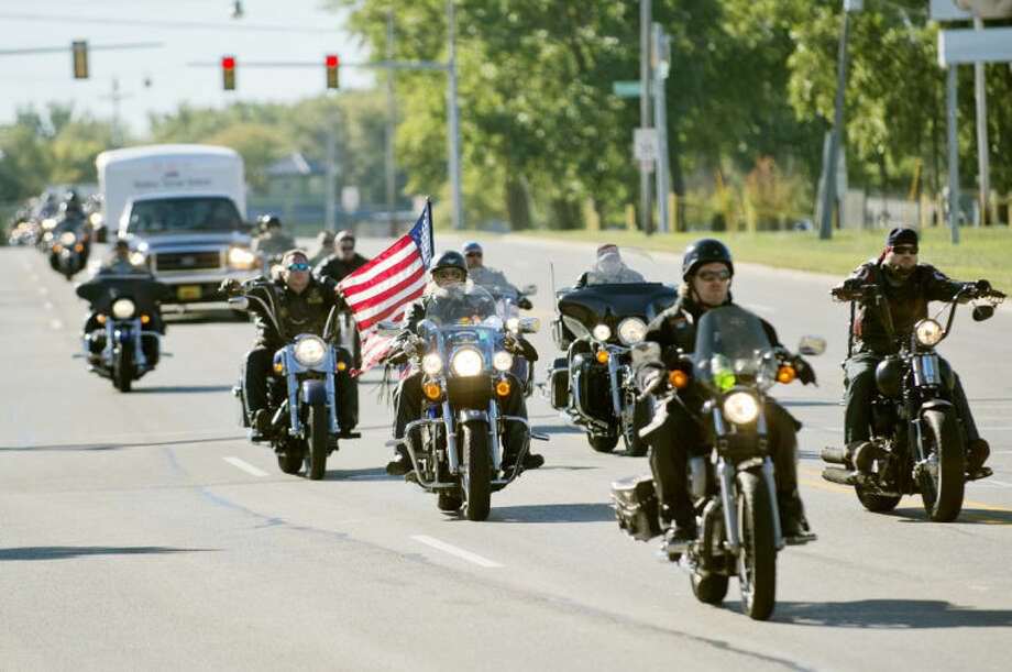 NICK KING | nking@mdn.net Motorcyclists escort the truck transporting the Michigan Vietnam Veteran Traveling Memorial on Saginaw Road on their way to Sanford American Legion Post 443. The memorial, which will be on display at the American Legion continuing on Sunday until about 3 p.m., lists the names of 2,654 Michigan veterans killed during the Vietnam War. Photo: Nick King/Midland  Daily News