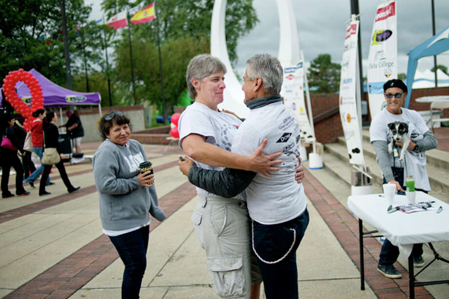 Donice Hannegan, left, of Midland, hugs Olympic diver Greg Louganis, right, during the AIDS Walk Great Lakes Bay Region Saturday at Wenonah Park in Bay City. Hannegan's partner Lisa Brockelbank, far left, and Louganis' fiancé Johnny Chaillot, far right, look on. Hannegan met Louganis earlier at a Gays, Lesbians and Allies at Dow event. Louganis came to the event to speak about overcoming challenges in his life. Louganis met with people, signed items and spoke at the Walk Rally. Photo: Nick King/Midland  Daily News / Midland Daily News