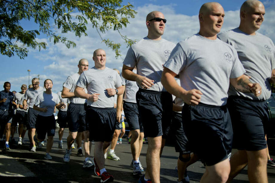 NICK KING | nking@mdn.netMembers of the Delta College Police Academy run during the Law Enforcement Torch Run Thursday at the Midland Law Enforcement Center. The run, which benefits Special Olympics, started at the Midland Law Enforcement Center and ended at Dow Diamond. Photo: Nick King/Midland  Daily News