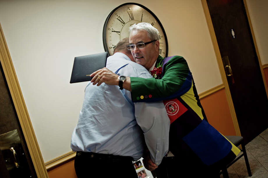 John Berry, of Freeland, hugs Tim Drudi, of Beaverton, after accepting the the Modern Woodmen Hometown Hero award Friday afternoon at M's Cafe in Midland. Photo: Sean Proctor/Midland  Daily News / Midland Daily News