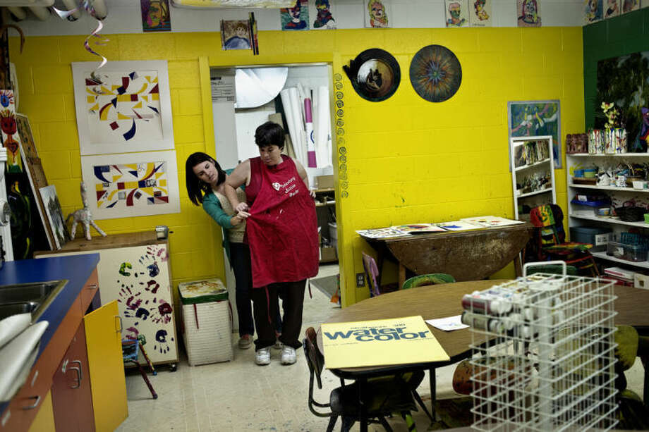SEAN PROCTOR | sproctor@mdn.netRachel Gaffney, program coordinator for Express Yourself Artshop, helps Colleen Dolan, of Midland, put an apron on Monday afternoon before their ceramics class at Creative 360. The new program encourages people to express themselves through their artwork, offering a variety of classes including ceramics, paper crafts, photography and metal smithing. Photo: Sean Proctor/Midland  Daily News