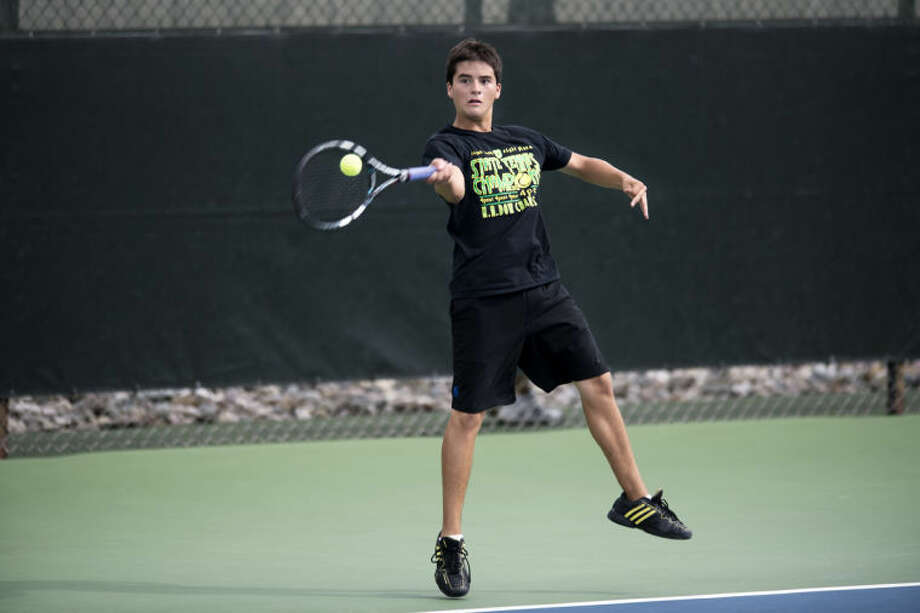 NEIL BLAKE | nblake@mdn.netDow's Julian Guerra hits the ball during the No. 2 singles match against Forest Hills Central's Bobby Lotzar at the Midland Community Tennis Center on Wednesday. Photo: Neil Blake/Midland  Daily News