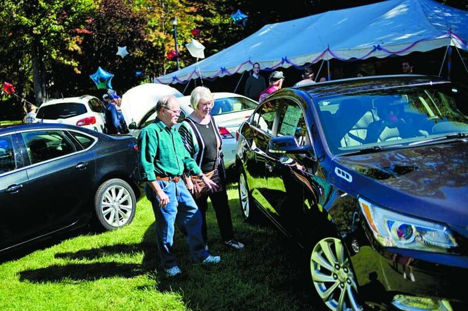 NICK KING | nking@mdn.net Mel Keim, left, and his wife Sherry check out the new Buick models at the company's display during the Northwood University Auto Show Friday on campus. The Keims were out checking out all the companies' new models. Photo: Nick King/Midland  Daily News
