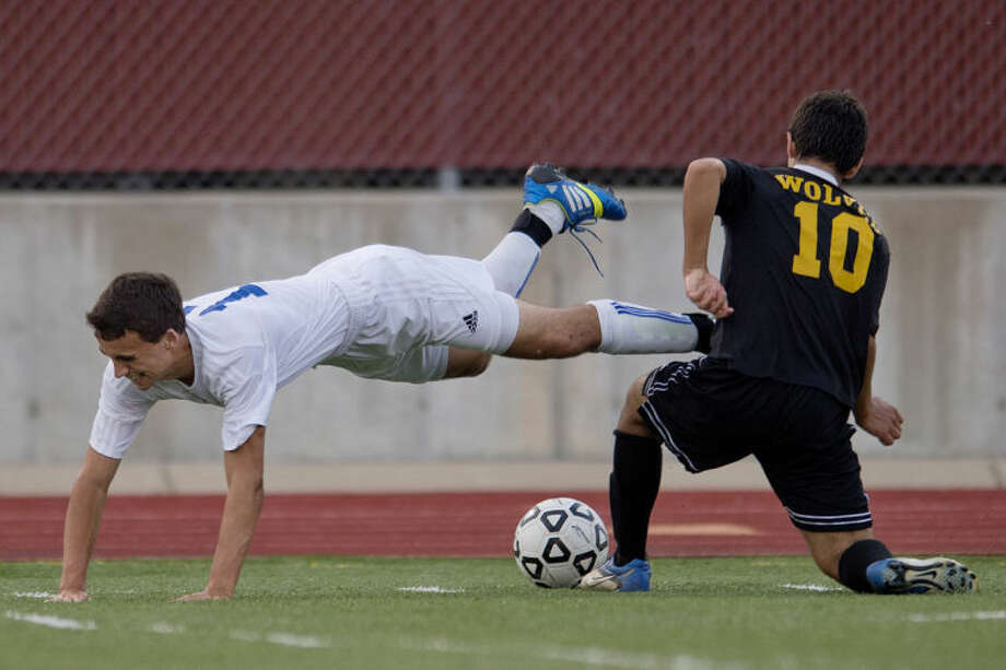 NICK KING | nking@mdn.netMidland's Greg Long, left, dives past Bay City Central's Daniel Damian in the first half Monday at Midland Community Stadium. The Chemics won 7-0. Photo: Nick King/Midland  Daily News
