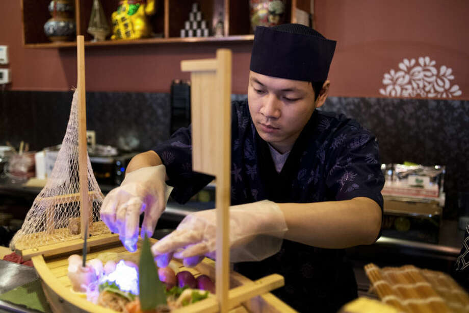 NEIL BLAKE | nblake@mdn.netChef Amin Dong at Fuji Sushi prepares a dish at the restaurant, which offers a variety of sushi dishes. Photo: Neil Blake/Midland  Daily News