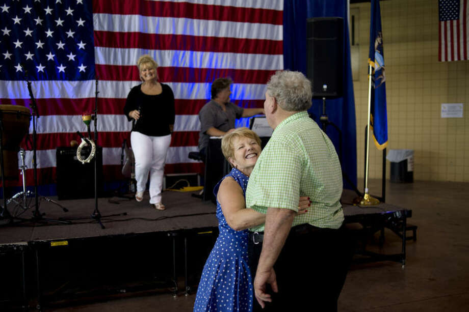 NICK KING | nking@mdn.netCarol Park, left, hugs Al Kloha at the end of their dance as Ernest Entertainment performs Monday during Michigan Attorney General Bill Schuette's annual barbecue at the Midland County Fairgrounds. Photo: Nick King/Midland  Daily News