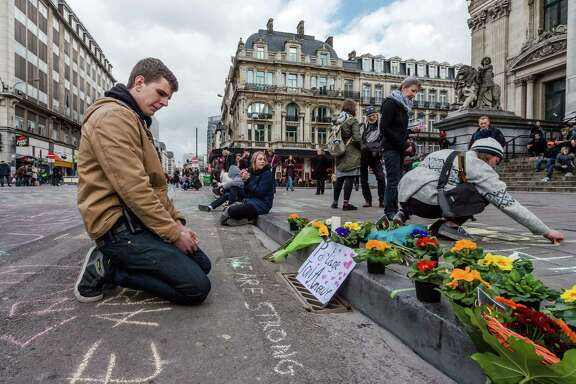 A man looks at flowers and messages outside the stock exchange in Brussels on Tuesday, March 22, 2016. Explosions, at least one likely caused by a suicide bomber, rocked the Brussels airport and subway system Tuesday, prompting a lockdown of the Belgian capital and heightened security across Europe. At least 26 people were reported dead.