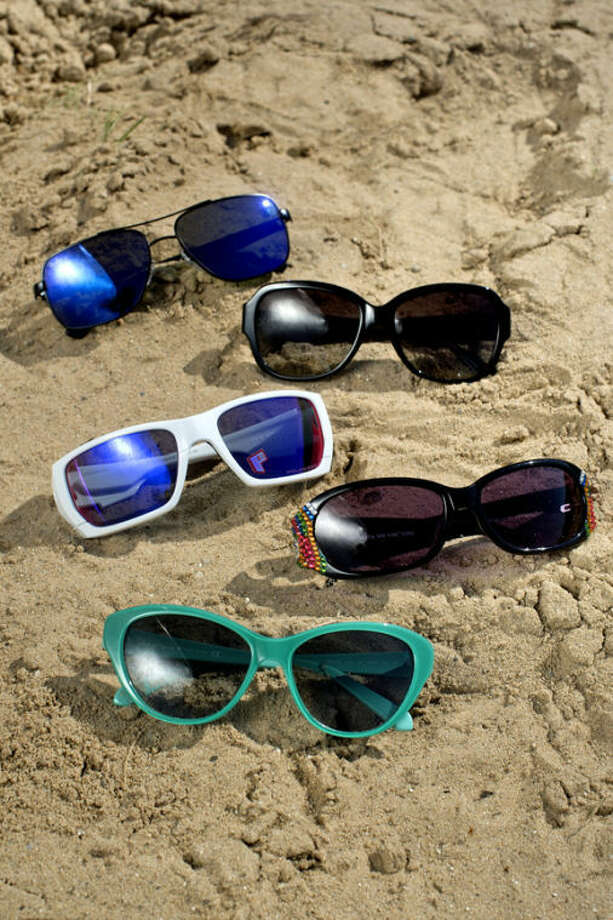 These five styles of sunglasses are sure to be seen at the beach or poolside. From top, sunglasses are from Ray-Ban, Coach, Oakley, Jimmy Crystal and Kate Spade. Sunglasses courtesy of Mid-Michigan Eye Care . Photo: NICK KING | Nking@mdn.net