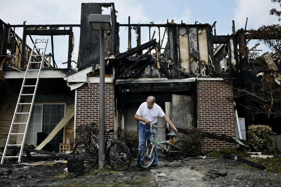 SEAN PROCTOR | sproctor@mdn.netGene Wright, of Midland, picks up a bike salvaged from his apartment and heads toward his truck Monday after a fire that destroyed his building at the Village at Joseph's Run. Wright had only lived in the apartment for three months with his newlywed wife, Susan. Photo: Sean Proctor/Midland  Daily News