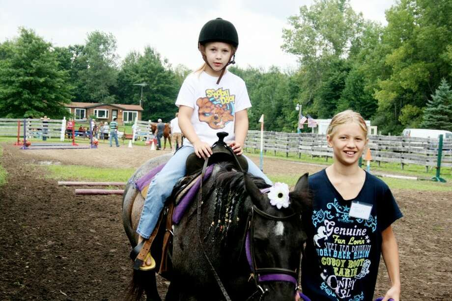 Tauri Hintz, 10, right, leads a horse while her cousin Breanne Young, 7, enjoys the ride at Camp Centaur. Photo: TRACY BURTON | For The Daily News