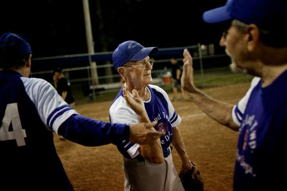 Bob Moe, 86, center, celebrates the Midland Township Fire Dept. 60-and-over slowpitch team's win over Pizza Sams with teammates Jerry Eisman, left, and Dave Broomfield Thursday at the Redcoat Softball Complex. Midland Township Fire Dept. won 14-9. Photo: NICK KING | Nking@mdn.net