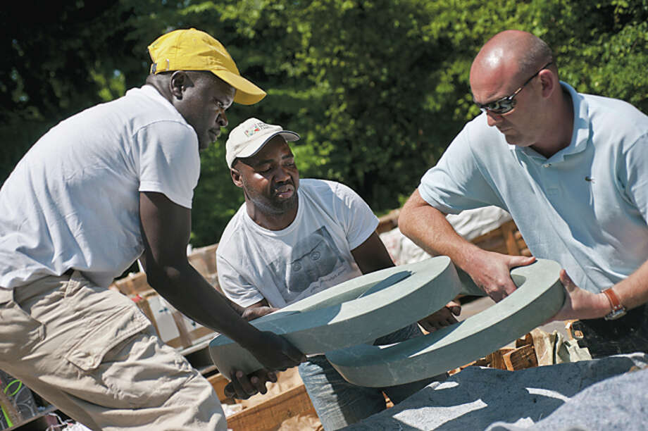 SEAN PROCTOR | sproctor@mdn.net From left, Passmore Mupindinko, Patrick Sephani and Joseph Croisette, of Zimbabwe, load a sculpture onto their cart Tuesday afternoon at Dow Gardens in preparation for the ZimSculpt exhibit, which features several dozen pieces of the finest in Zimbabwean rock sculpture worldwide. The exhibit will be on display from Saturday, June 22 through Sunday, August 4. Photo: Sean Proctor/Midland  Daily News / Midland Daily News