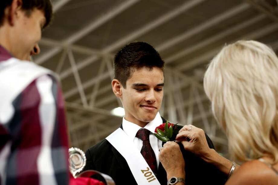 THOMAS SIMONETTI | tsimonetti@mdn.netMichael Humphrey, 17, of Midland is crowned 2011 Midland County Fair King by last year's king, Andrew Weaver, 18, left, and pageant co-chairwoman Carolyn Myers on Saturday. Photo: Thomas Simonetti/Midland  Daily