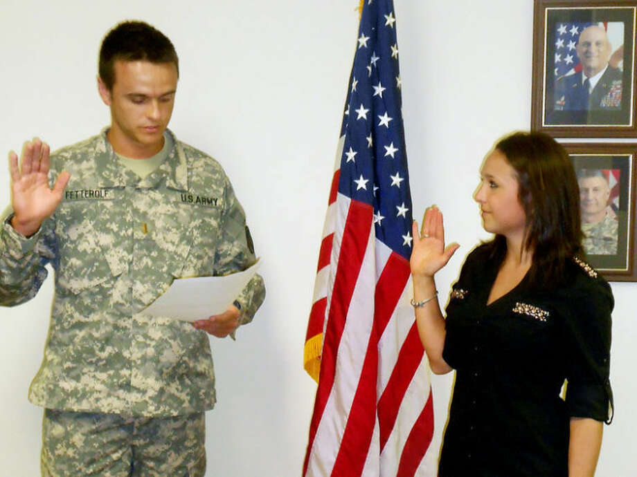 Brandon Fetterolf, left, swears his sister Brittany into the Army.