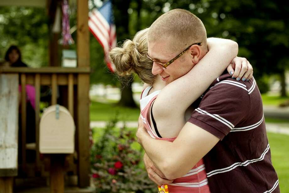 THOMAS SIMONETTI | tsimonetti@mdn.netNational Guard soldier Tim Forgie, right, hugs his sister Anita Forgie after returning home from a year of service in Kuwait. Photo: Thomas Simonetti/Midland  Daily