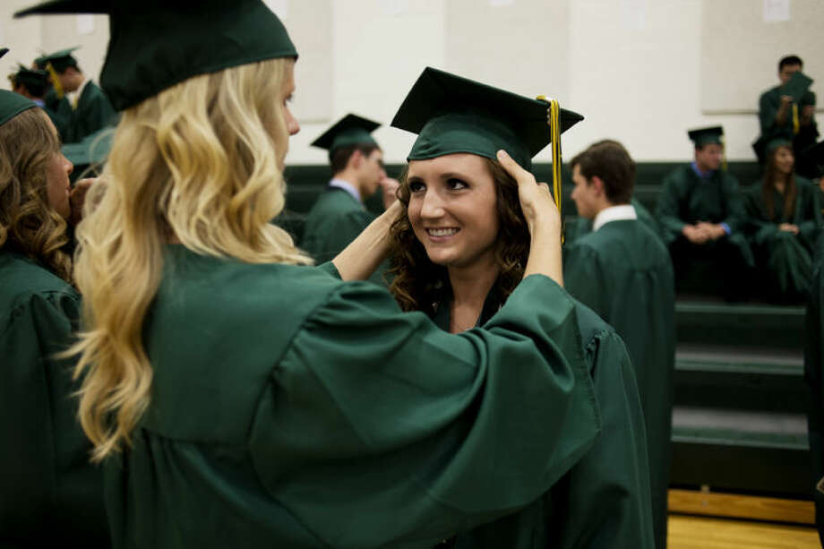NEIL BLAKE | nblake@mdn.net H.H Dow High School seniors Sarah Michalowski, 17, left, adjusts Jennifer Jacobs' graduation cap before their commencement ceremony on Friday. Photo: Neil Blake/Midland  Daily News