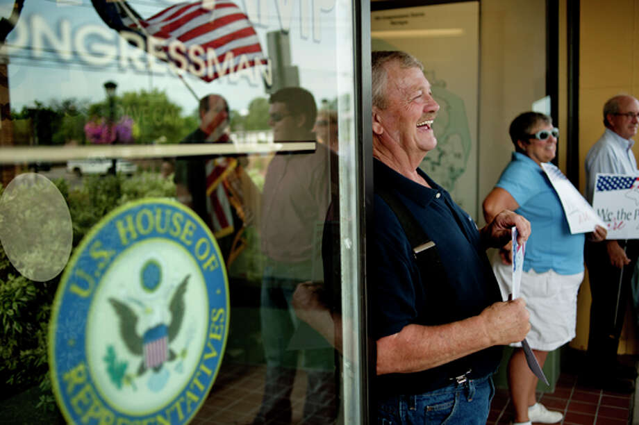 Roland Davidson, left, and Linda Roth, both from Midland, join the 30 or so people who rallied outside Rep. Dave CampÕs Midland office on Tuesday afternoon. The protest, which was organized by the group We Are The People, was aimed at promoting job creation. Photo: NICK KING | Nking@mdn.net  / Midland Daily News